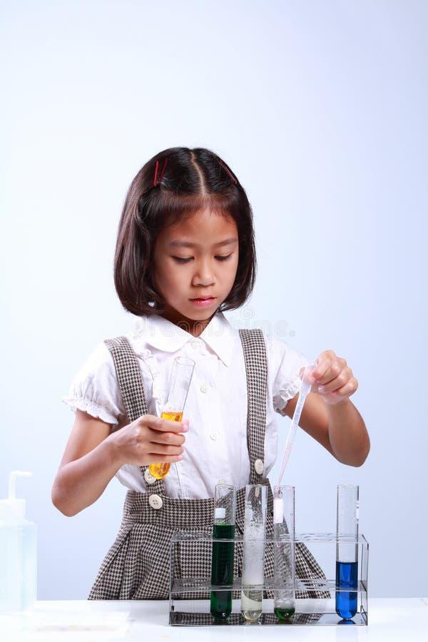 Kleines Mädchen, das ein Reagenzglas mit flüssiger Wissenschaftlerchemie und -wissenschaft hält lizenzfreie stockfotografie