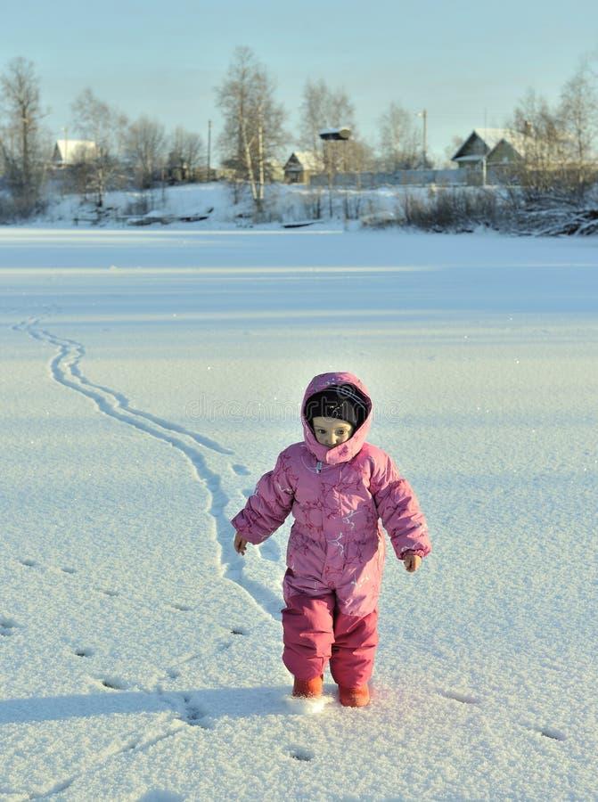 Kleines Mädchen, das ein rosa und ein Rot spielend und in ein schönes Feld des verschneiten Winters laufend trägt lizenzfreie stockbilder