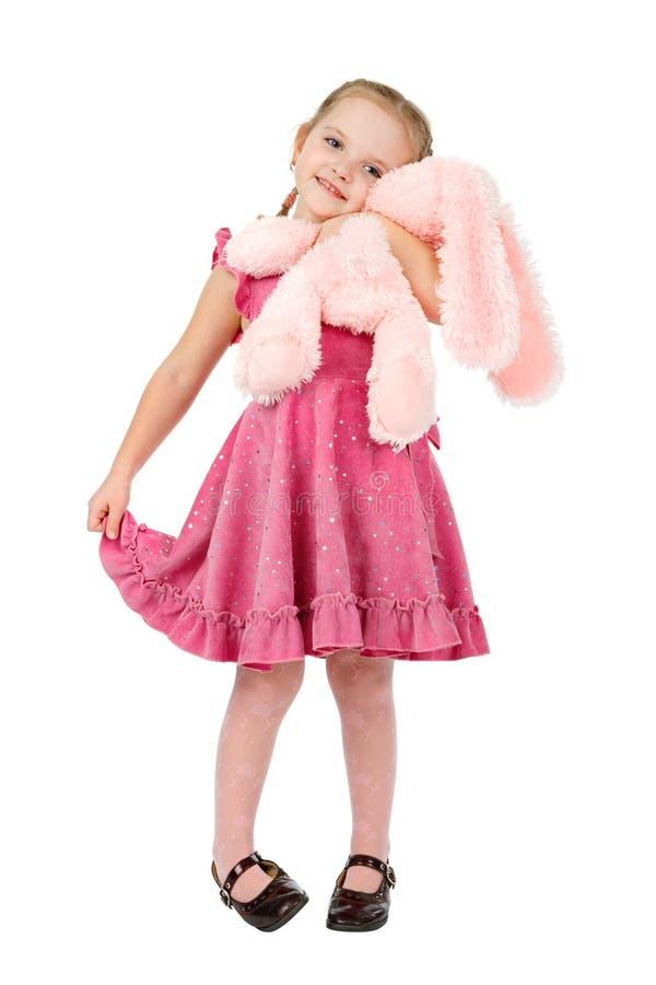 Kleines Mädchen, das ein rosafarbenes Spielzeugkaninchen umarmt stockfotos