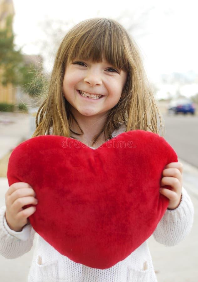 Kleines Mädchen, das ein rotes Inneres anhält lizenzfreie stockbilder