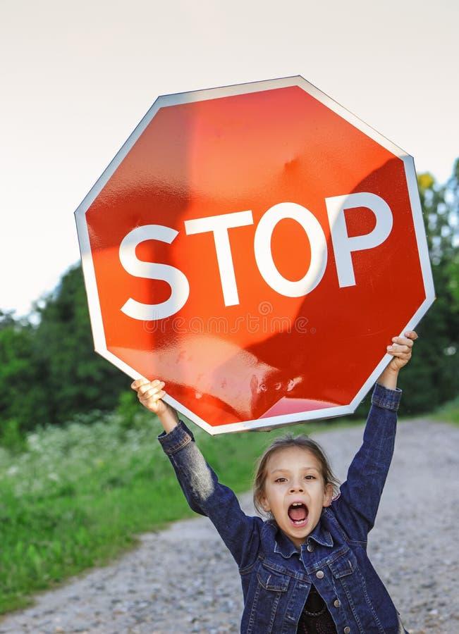 Kleines Mädchen, das ein rotes Zeichen hält stockbild