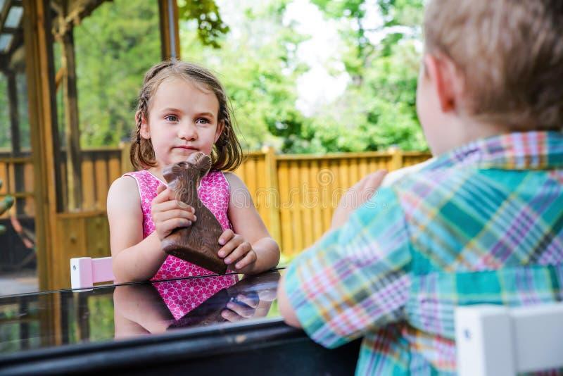 Kleines Mädchen, das ein Schokoladen-Häschen hält lizenzfreie stockfotos