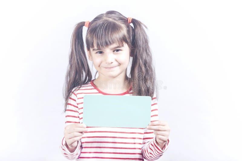 Kleines Mädchen, das ein unbelegtes Zeichen anhält stockbilder