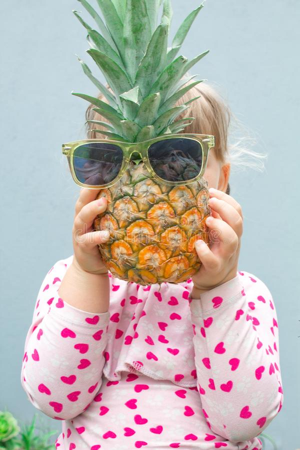 Kleines Mädchen, das eine Ananas mit Gläsern vor ihrem Gesicht hält Ananas anstelle des Kopfes Im Garten draußen stockfoto