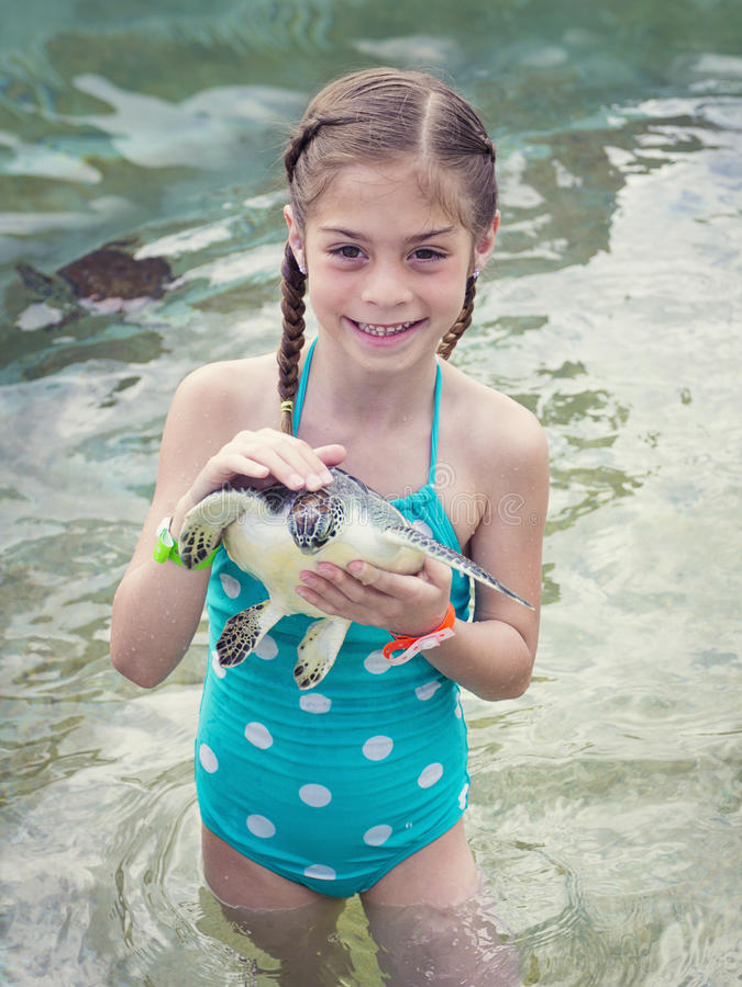 Kleines Mädchen, das eine Babymeeresschildkröte hält stockfotos