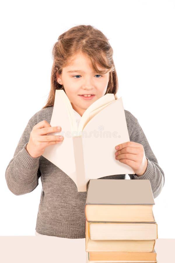 Kleines Mädchen, das eine Schuluniform liest ein Buch trägt stockfoto