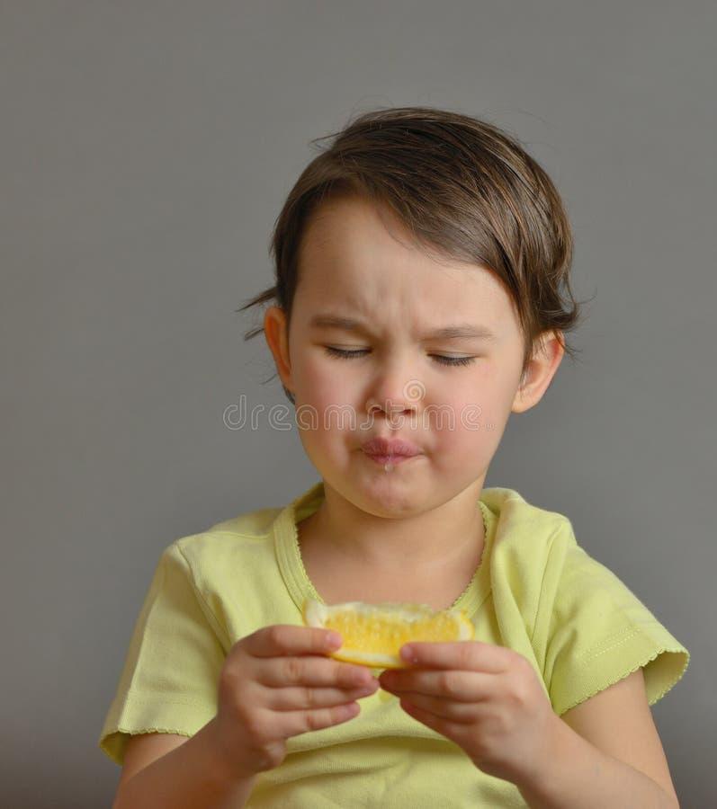 Kleines Mädchen, das eine Zitrone lokalisiert isst stockfotos