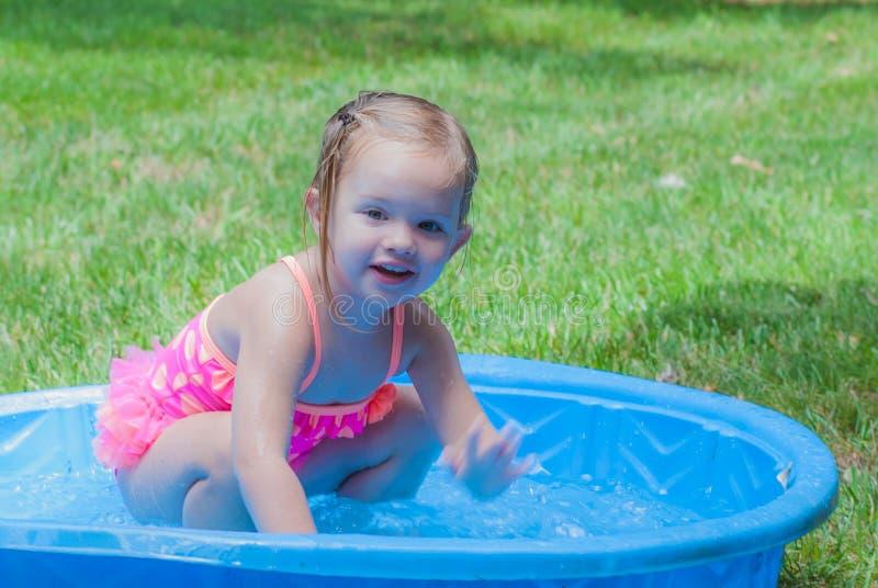 Kleines Mädchen, das in einem Kiddie-Pool spielt lizenzfreies stockfoto