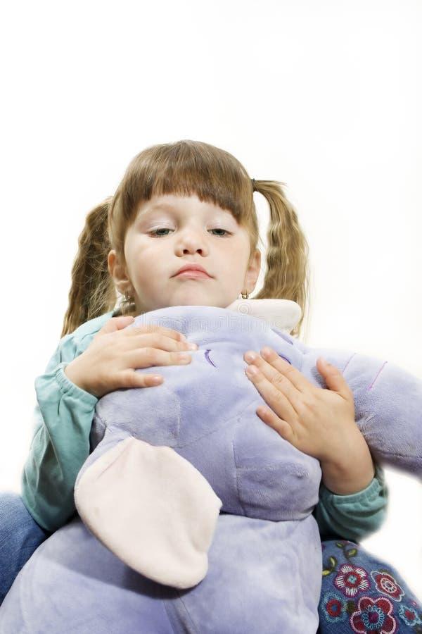 Kleines Mädchen, das einen angefüllten Elefanten streichelt. lizenzfreie stockfotos