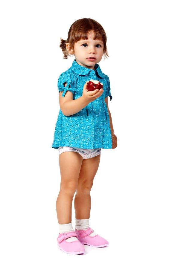 Kleines Mädchen, das einen Apfel isst stockfoto