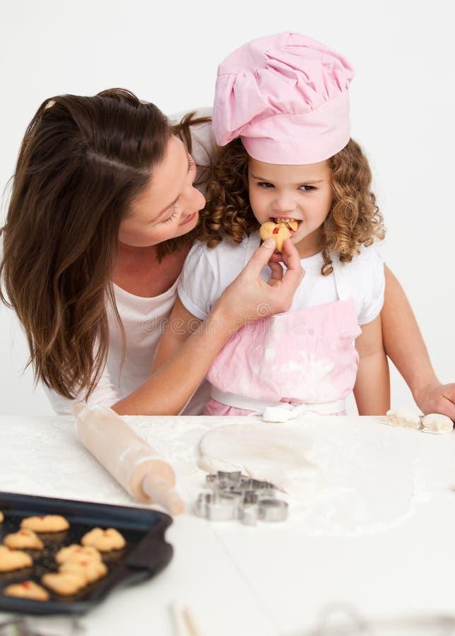 Kleines Mädchen, das einen Biskuit mit ihrer Mutter schmeckt stockfoto