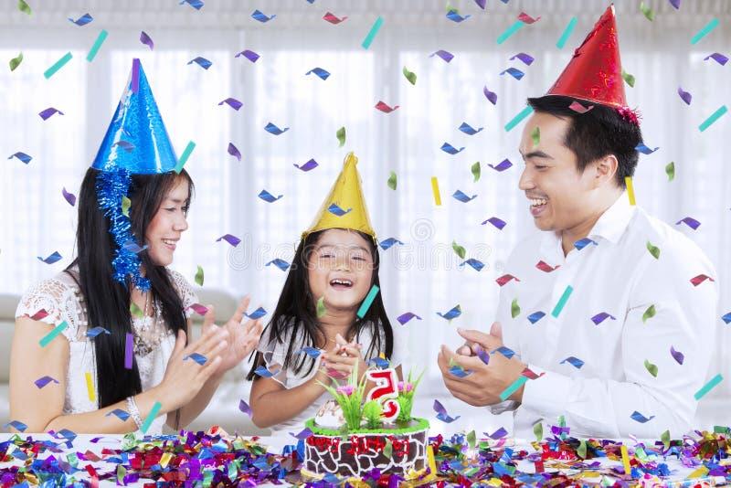 Kleines Mädchen, das einen Geburtstag mit ihren Eltern feiert stockfoto