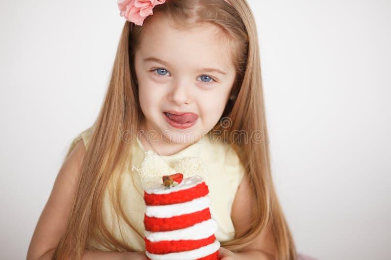 Kleines Mädchen, das einen Geburtstag mit rotem Kuchen feiert stockfotos