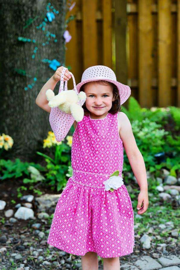Kleines Mädchen, das einen Geldbeutel mit einem Osterhasen hält lizenzfreie stockbilder