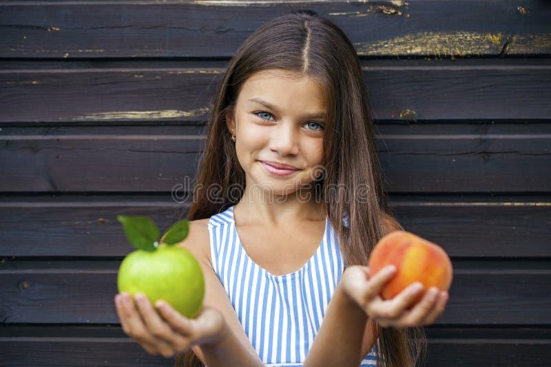 Kleines Mädchen, das einen grünen Apfel und einen Pfirsich hält stockfotografie