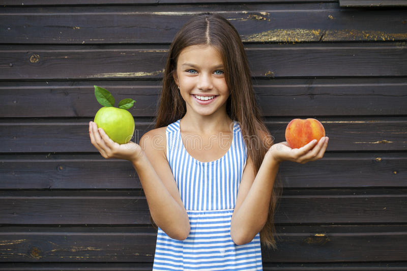 Kleines Mädchen, das einen grünen Apfel und einen Pfirsich hält lizenzfreie stockfotografie