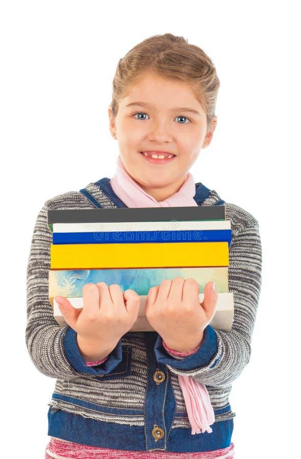 Kleines Mädchen, das einen großen Stapel von Büchern hält stockfotografie