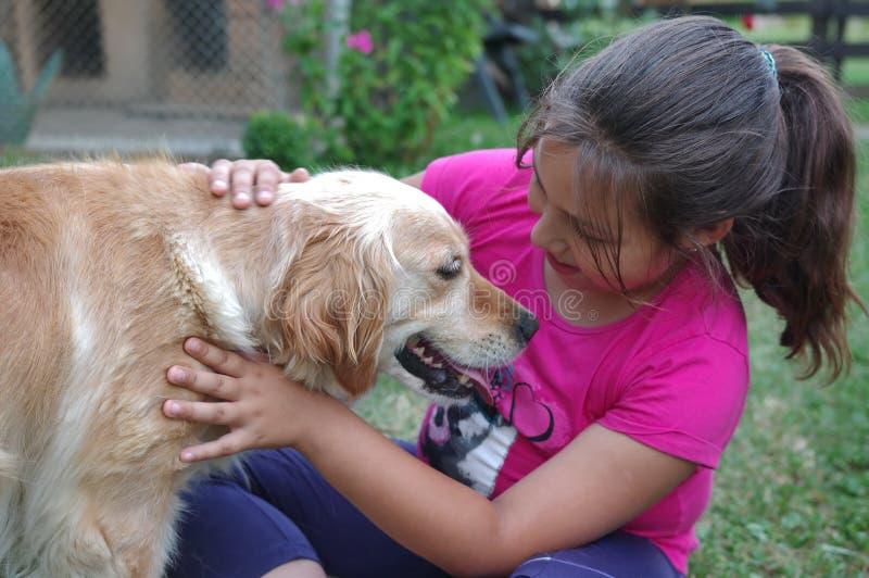 Kleines Mädchen, das einen Hund streicht stockbilder