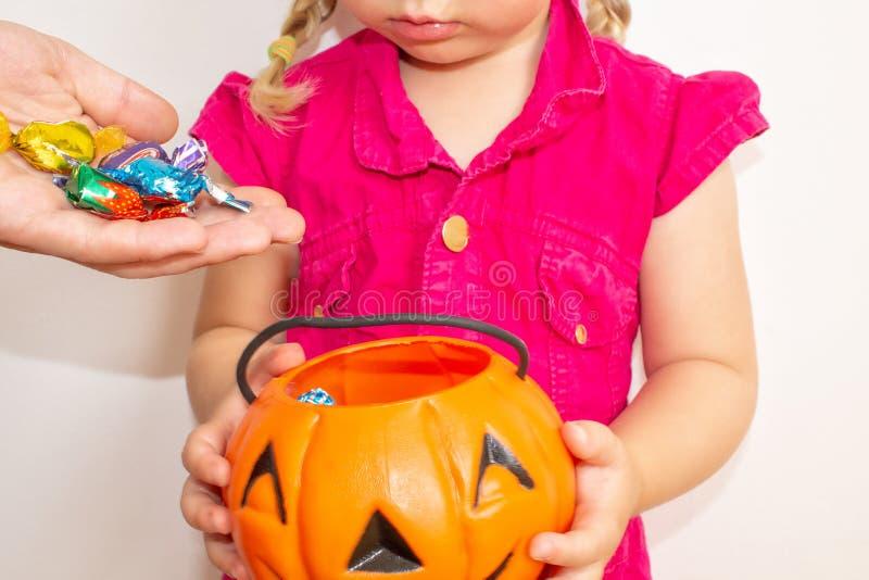 Kleines Mädchen, das einen Kürbis mit Süßigkeiten in ihren Händen, auf Halloween hält Erwachsenleute legten Süßigkeit Kindern in  lizenzfreie stockbilder