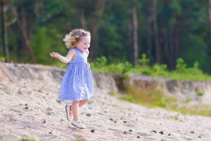 Kleines Mädchen, das in einen Kiefernwald läuft stockfoto