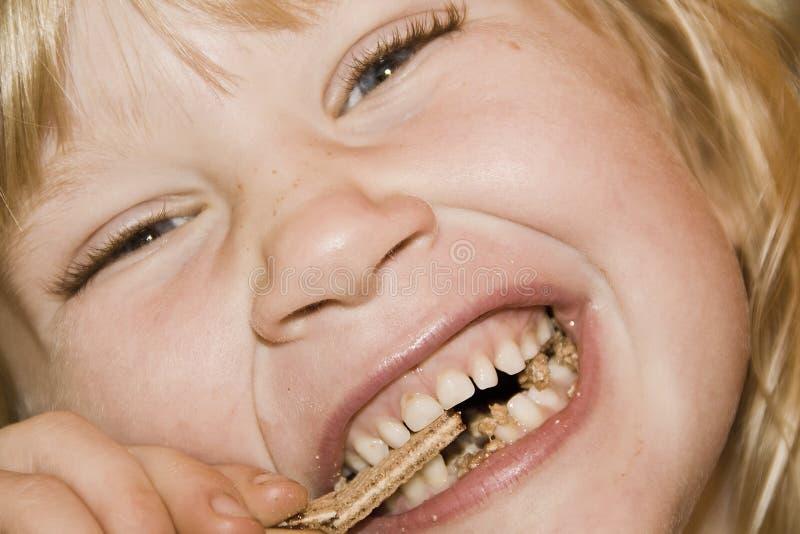 Kleines Mädchen, das einen Kuchen isst stockbild