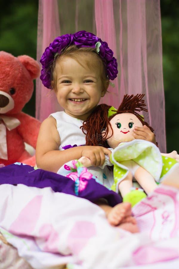 Kleines Mädchen, das einen purpurroten Kranz hält eine Puppe und ein Lächeln trägt stockfoto
