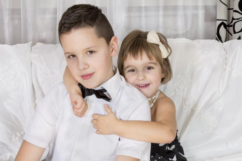 Kleines Mädchen, das einen schönen Jungenherrn umarmt stockfotografie