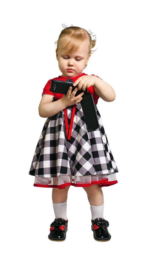 Kleines Mädchen, das einen Smartphone auf weißem Isolat hält stockfotografie