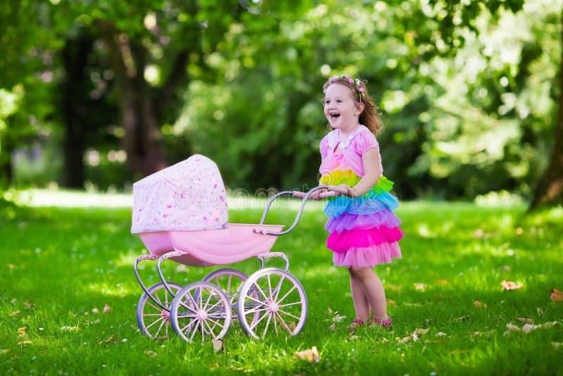 Kleines Mädchen, das einen Spielzeugspaziergänger mit Puppe drückt stockfotografie