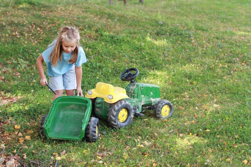 Kleines Mädchen, das einen Traktor repariert stockfoto