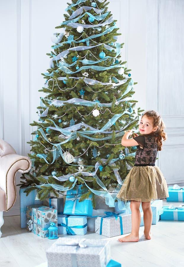 Kleines Mädchen, das einen Weihnachtsbaum verziert stockbilder