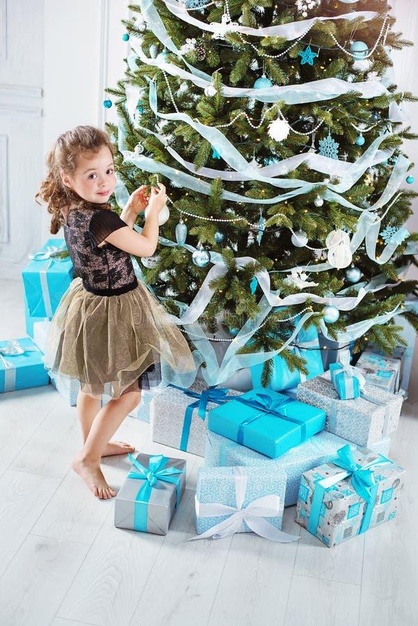 Kleines Mädchen, das einen Weihnachtsbaum verziert lizenzfreies stockfoto