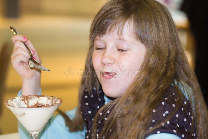 Kleines Mädchen, das Eiscreme im Café isst stockfotografie