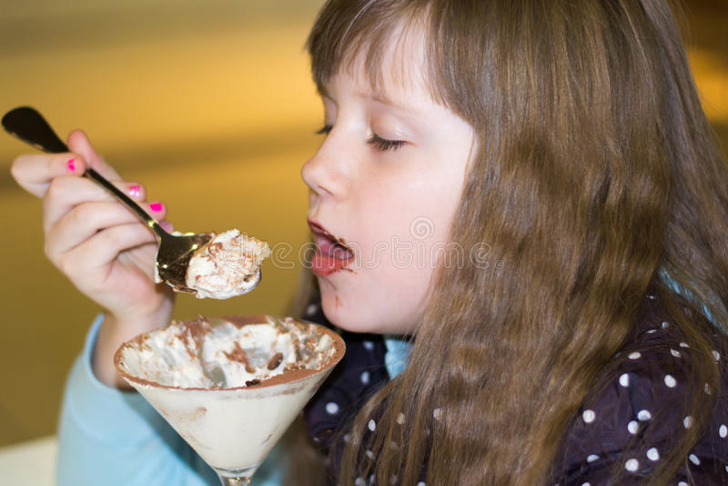 Kleines Mädchen, das Eiscreme im Café isst stockfoto