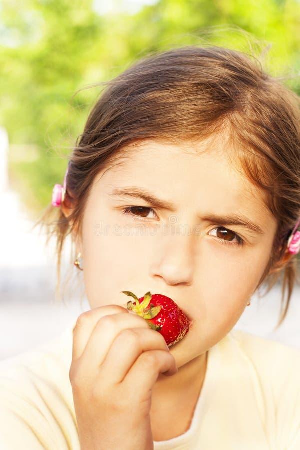 kleines Mädchen, das Erdbeeren isst lizenzfreie stockbilder