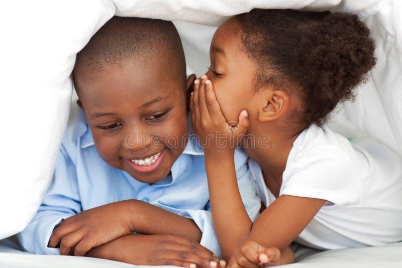 Kleines Mädchen, das etwas zu ihrem Bruder flüstert stockbild