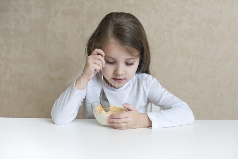 Kleines Mädchen, das Frühstück muesli mit Milch hat lizenzfreie stockfotografie