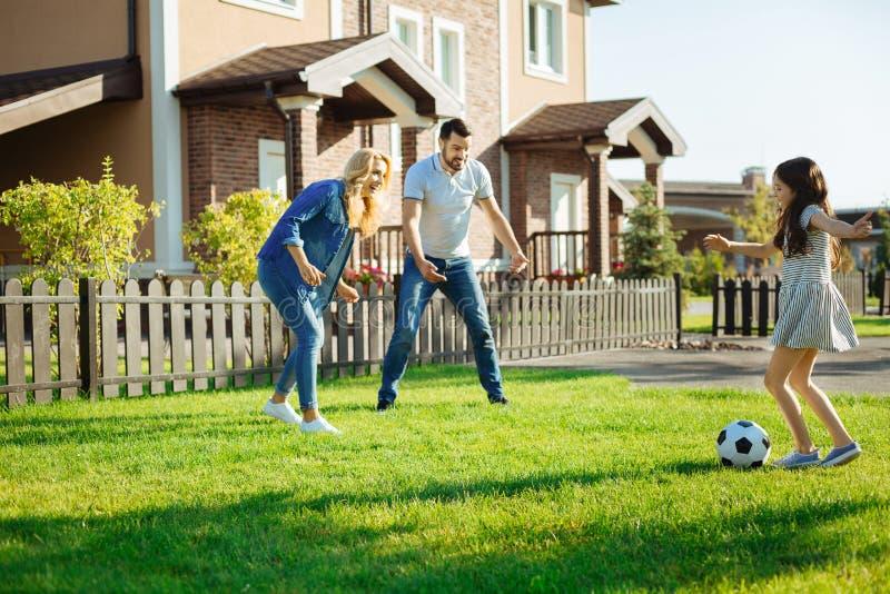 Kleines Mädchen, das Fußball mit ihren Eltern spielt stockfoto