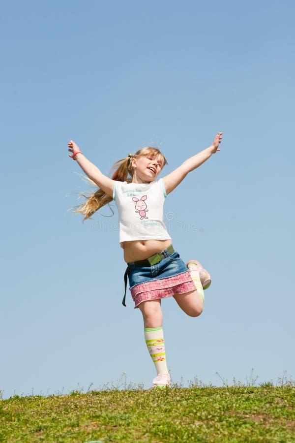 Kleines Mädchen, das gegen schönen Himmel springt lizenzfreie stockfotos