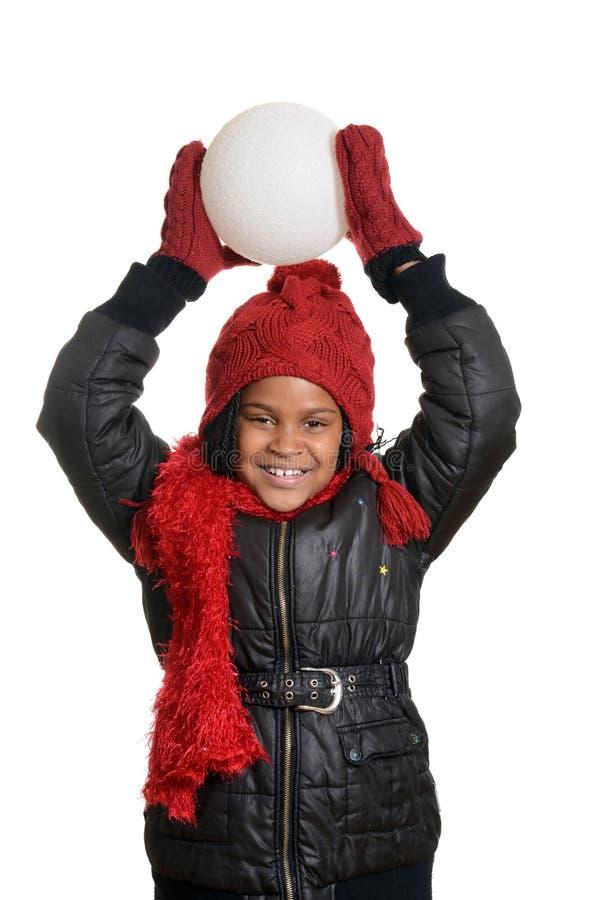 Kleines Mädchen, das geht, einen Schneeball zu werfen stockbild