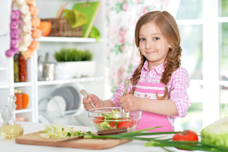 Kleines Mädchen, das Gemüsesalat zubereitet stockbild