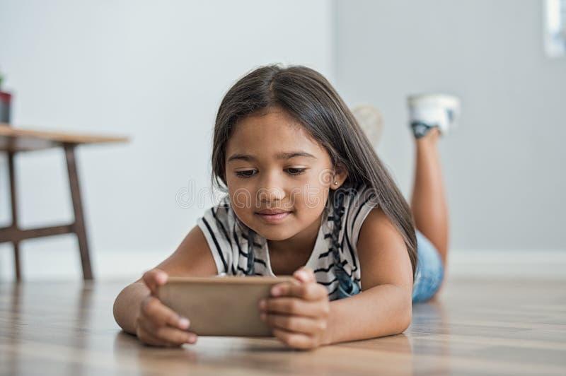 Kleines Mädchen, das Handy verwendet lizenzfreies stockbild