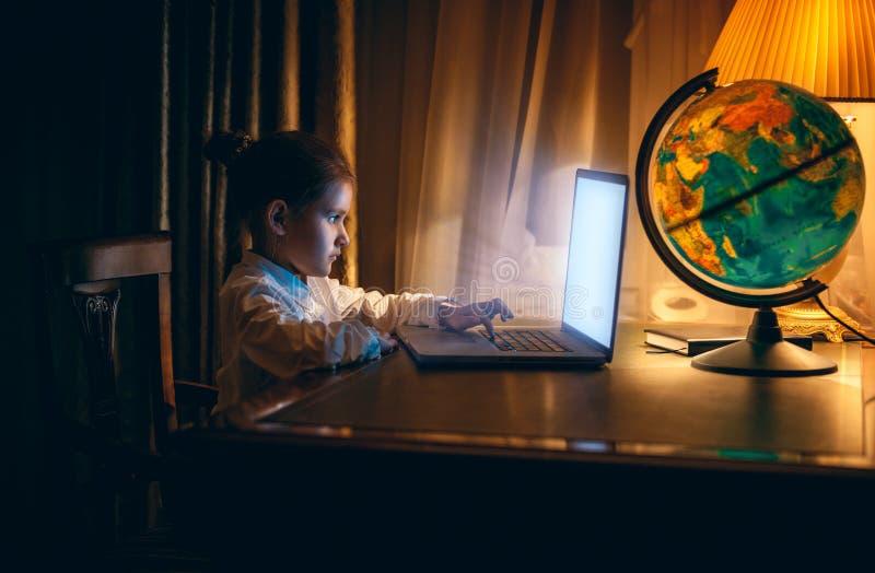 Kleines Mädchen, das Hausarbeit auf Laptop am Abend tut lizenzfreie stockbilder