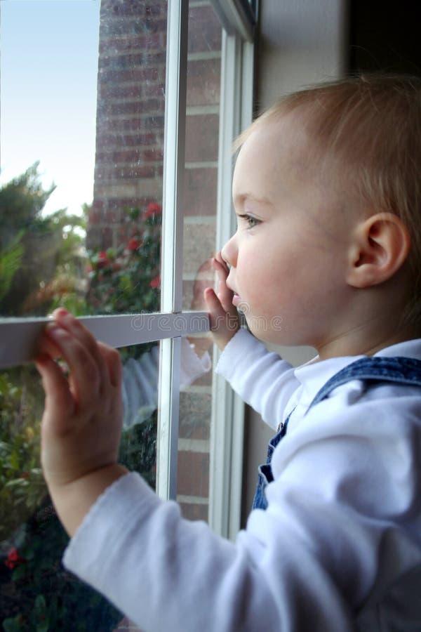 Kleines Mädchen, das heraus ein Fenster schaut lizenzfreie stockfotos