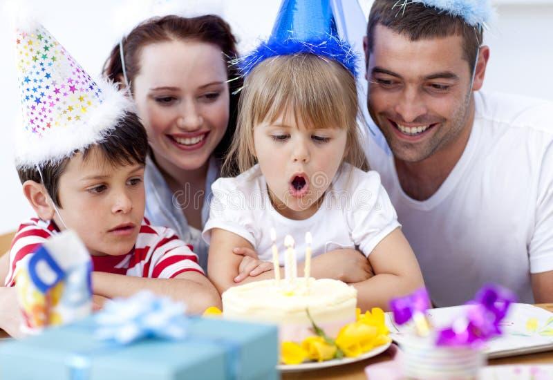 Kleines Mädchen, das heraus Kerzen in ihrem Geburtstag durchbrennt stockfotos