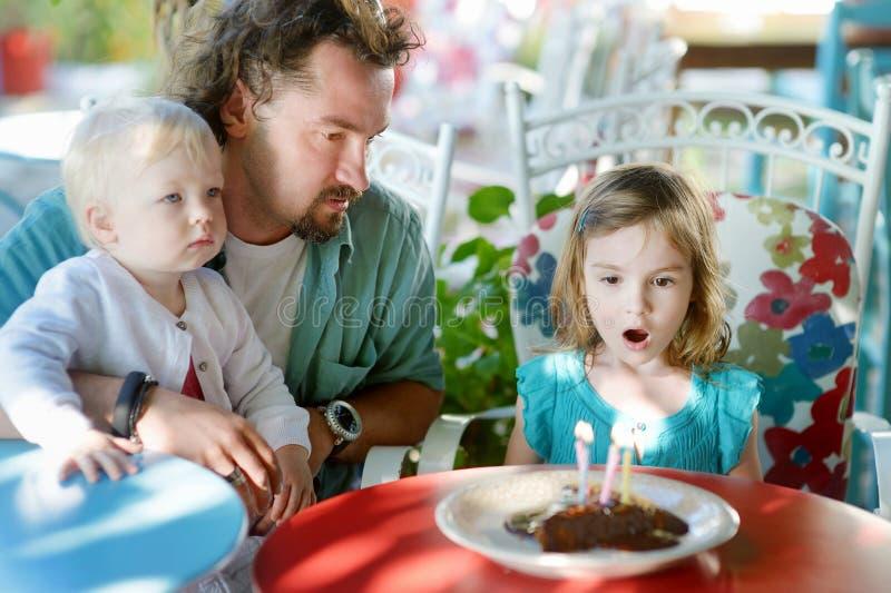 Kleines Mädchen, das heraus Kerzen in ihrem Geburtstag durchbrennt lizenzfreie stockfotos