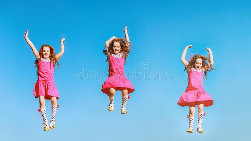 Kleines Mädchen, das in Himmelhintergrund springt oder tanzt lizenzfreies stockbild