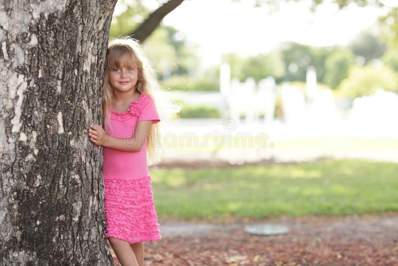 Kleines Mädchen, das hinter dem Baum aufwirft stockbild