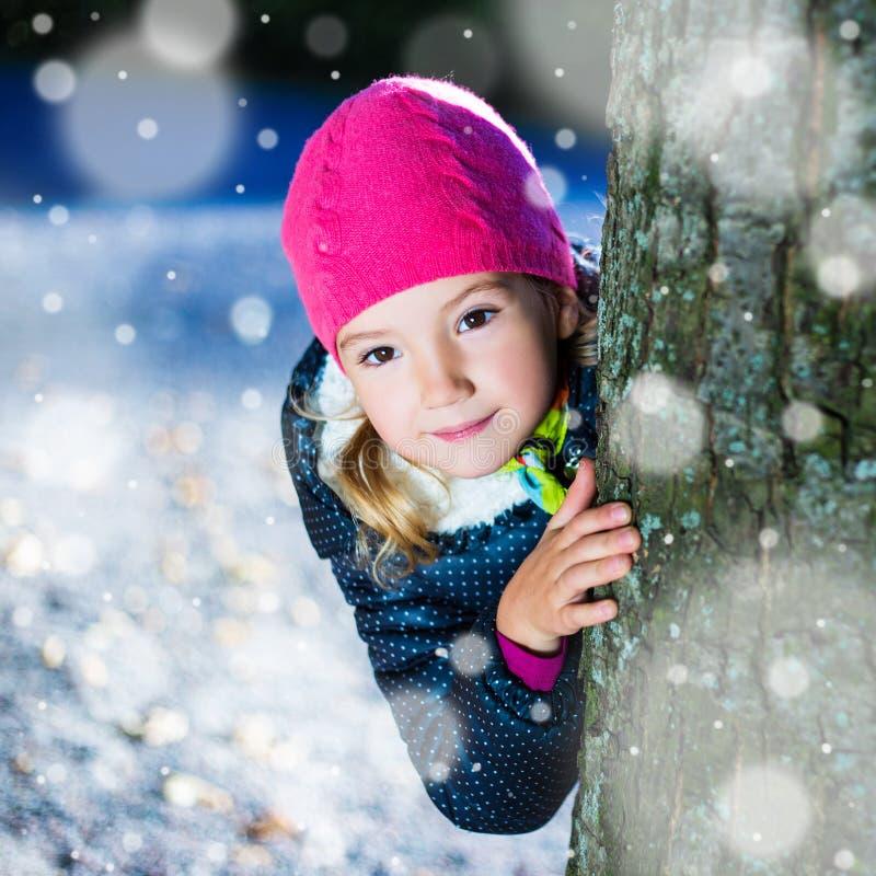 Kleines Mädchen, das hinter einem Baum im Winterpark sich versteckt stockbild