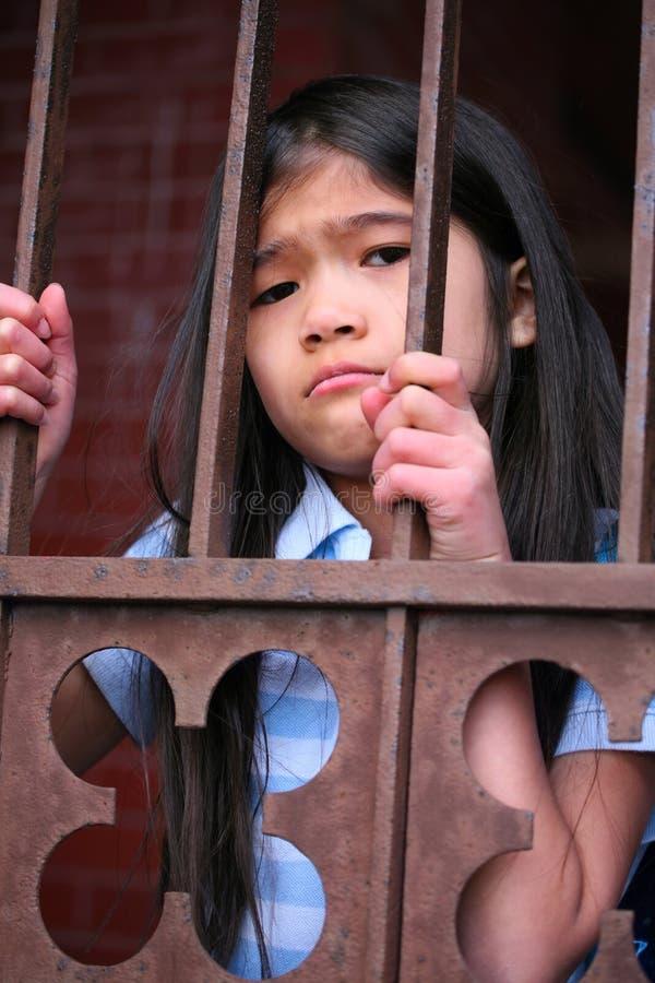 Kleines Mädchen, das hinter Eisenstangen steht stockfoto